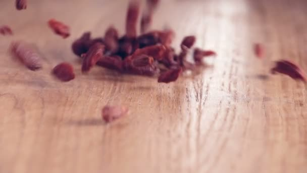 Banda Goji bobule autentické-zpomaleně padající na dřevěný stůl, zblízka