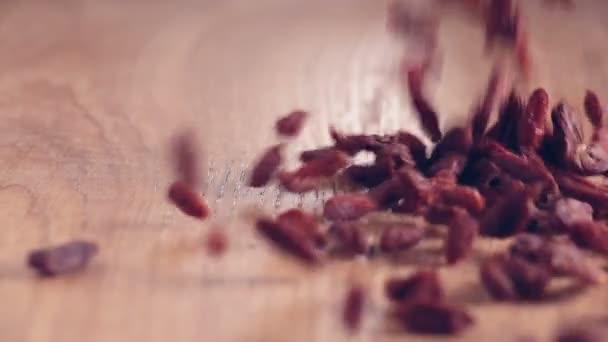 Super Food Goji-Beeren gleichmäßig auf Holztisch in Küche gegossen, authentische Zeitlupe in Großaufnahme.