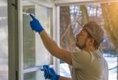 mladý muž používá hadr a stěrku při čištění oken, profesionální okno čisticí kazetu