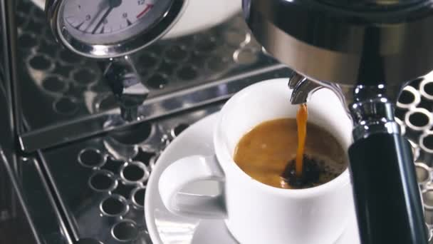 Espresso pouring from classic coffee machine into small white cup. Close-up Shot.