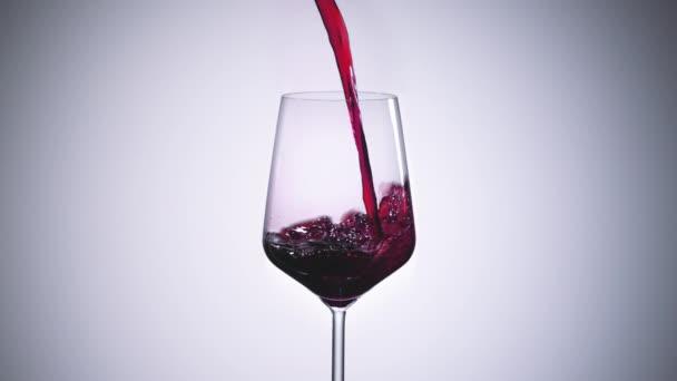 super zpomalený vysokorychlostní záběr červeného vína tekoucího do velkého bordeaux vinného skla - záběr ultra rychlostní kamerou