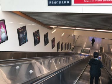 people on moving staircase in Beijing subway