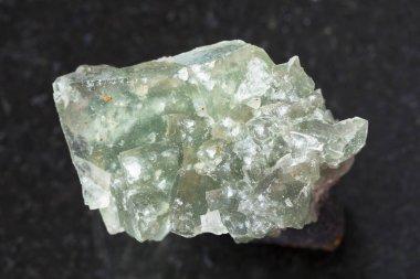 green crystalline fluorite gemstone on dark
