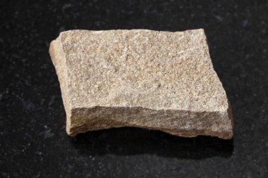 raw polymictic sandstone stone on dark