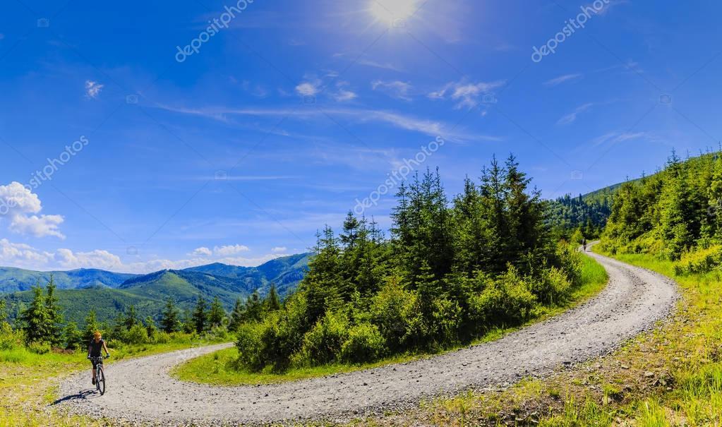 Фотообои Mountain biking women riding on bike in summer mountains forest