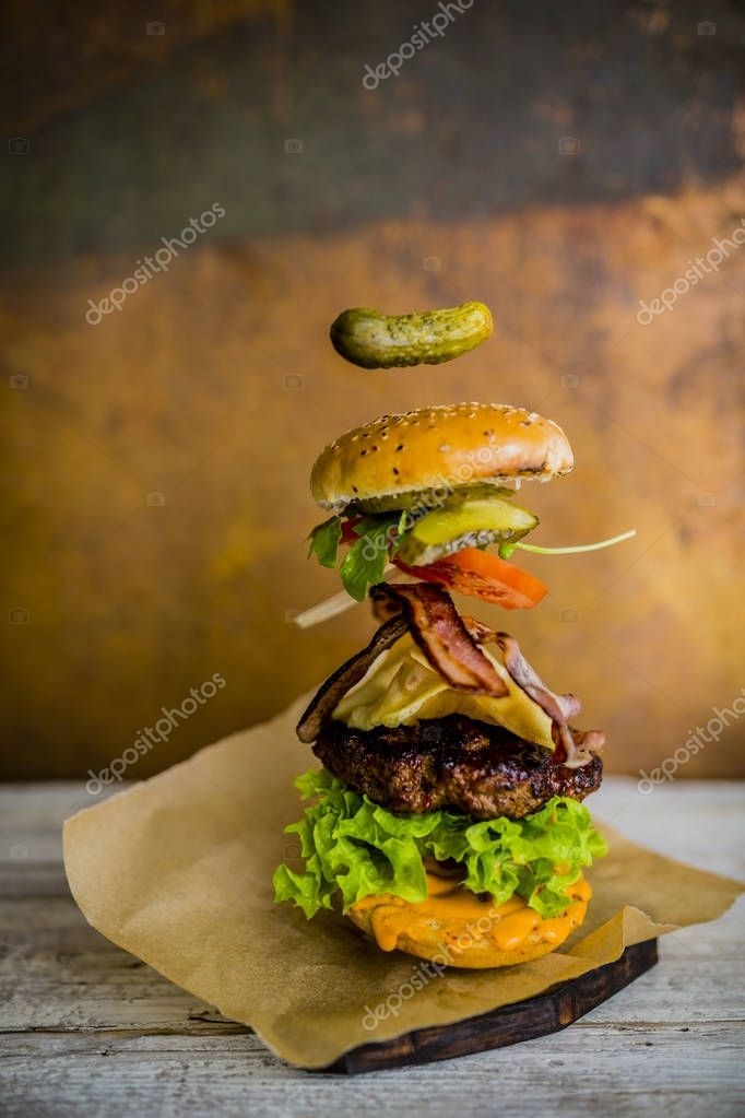 Hamburger with realistic flying ingredients. Tasty smoked grille