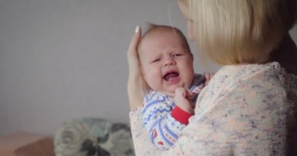 Mladá matka drží a houpání její holčička doma.