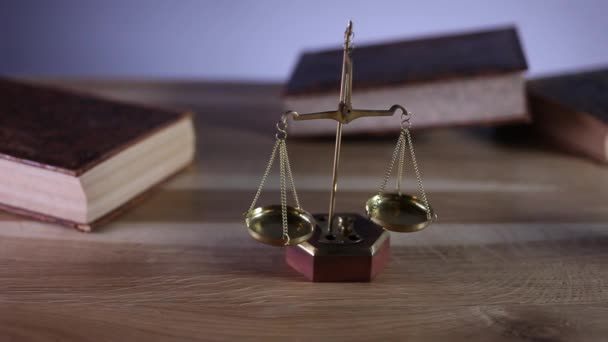 Law and justice concept.  Paragraphs, gavel and books on wooden table, dolly shot.