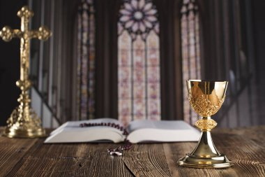 Holy communion concept. The Cross, Holy Bible, rosary and golden chalice.