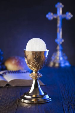First holy communion theme. The Cross, Holy Bible, rosary and golden chalice. Bread and grapes  symbols of Christianity.