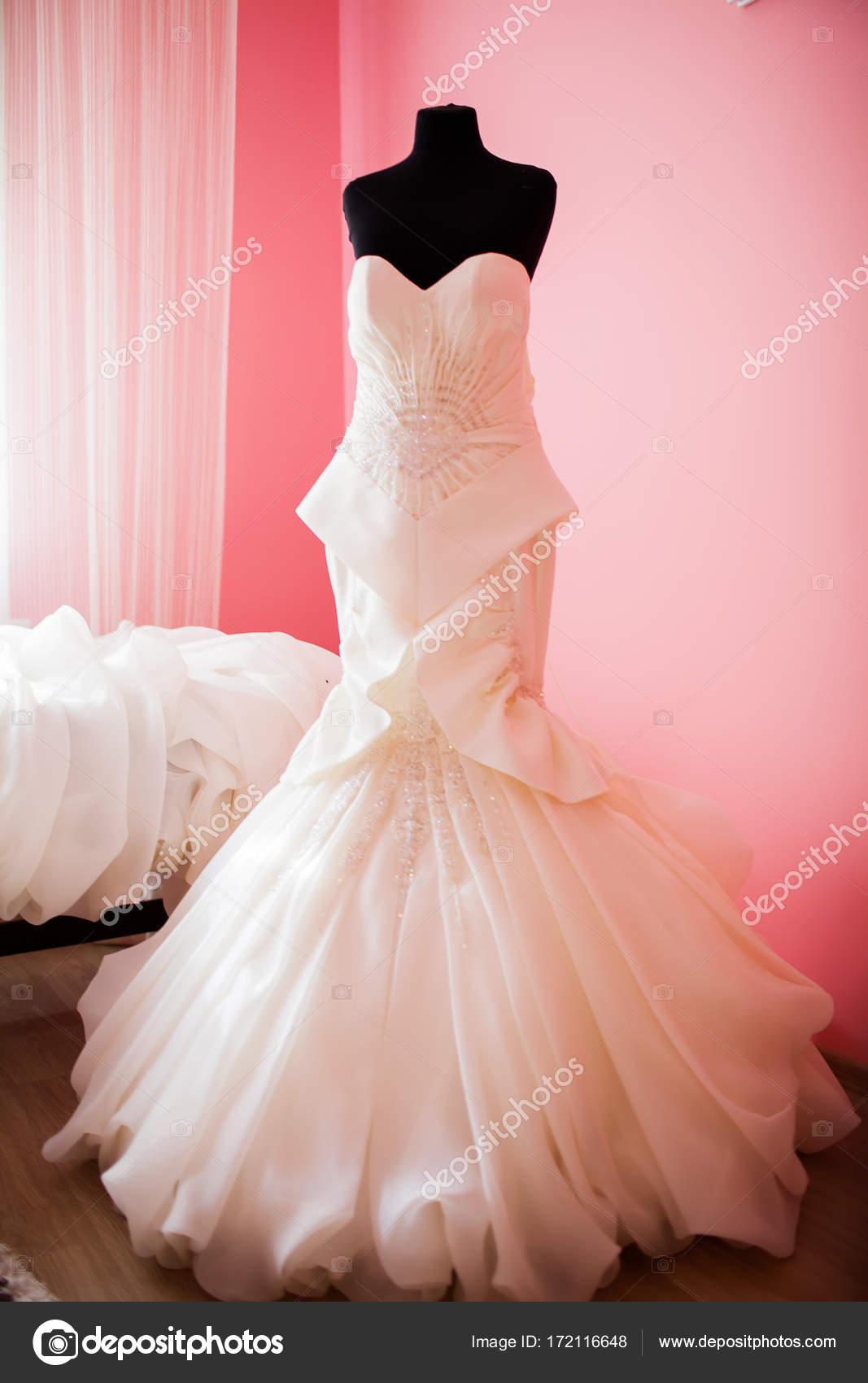 Vestido de novia colgadas en un maniquí en una habitación de la ...