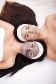 Využívání obličejovou masku na obličej dvě mladé ženy v salonu krásy