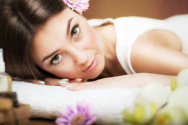 Massage. Beautiful woman at the spa. Gentle look. Flowers in hair. The concept of health and beauty. Dark background. Spa salon.