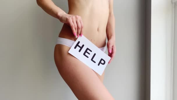 Gesundheitsprobleme bei Frauen. Nahaufnahme einer Frau mit schlankem Körper in Höschen, die eine weiße Karte mit Worthilfe in der Nähe ihres Bauches hält. Verdauungsstörungen, Periodenschmerzen, gesundheitliche Probleme.