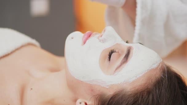 Junge Schönheit besucht Wellness-Salon und bekommt Gesichtsmaske zur Gesichtspflege