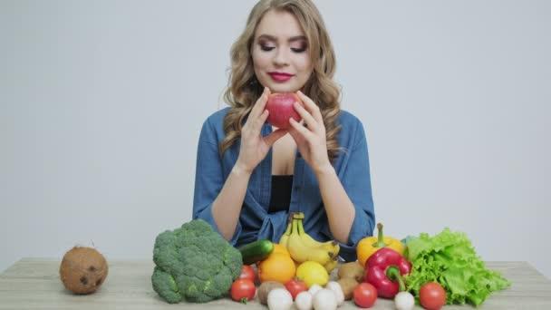 Egészséges ételek otthon, nő a konyhában friss zöldségekkel és gyümölcsökkel a fehér falon háttér