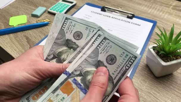 Muž počítá 100 dolarů bankovky obdržené na studentské půjčky