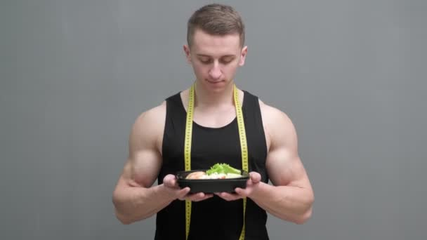 Healthy eating concept. Man of athletic build eats healthy food high in protein