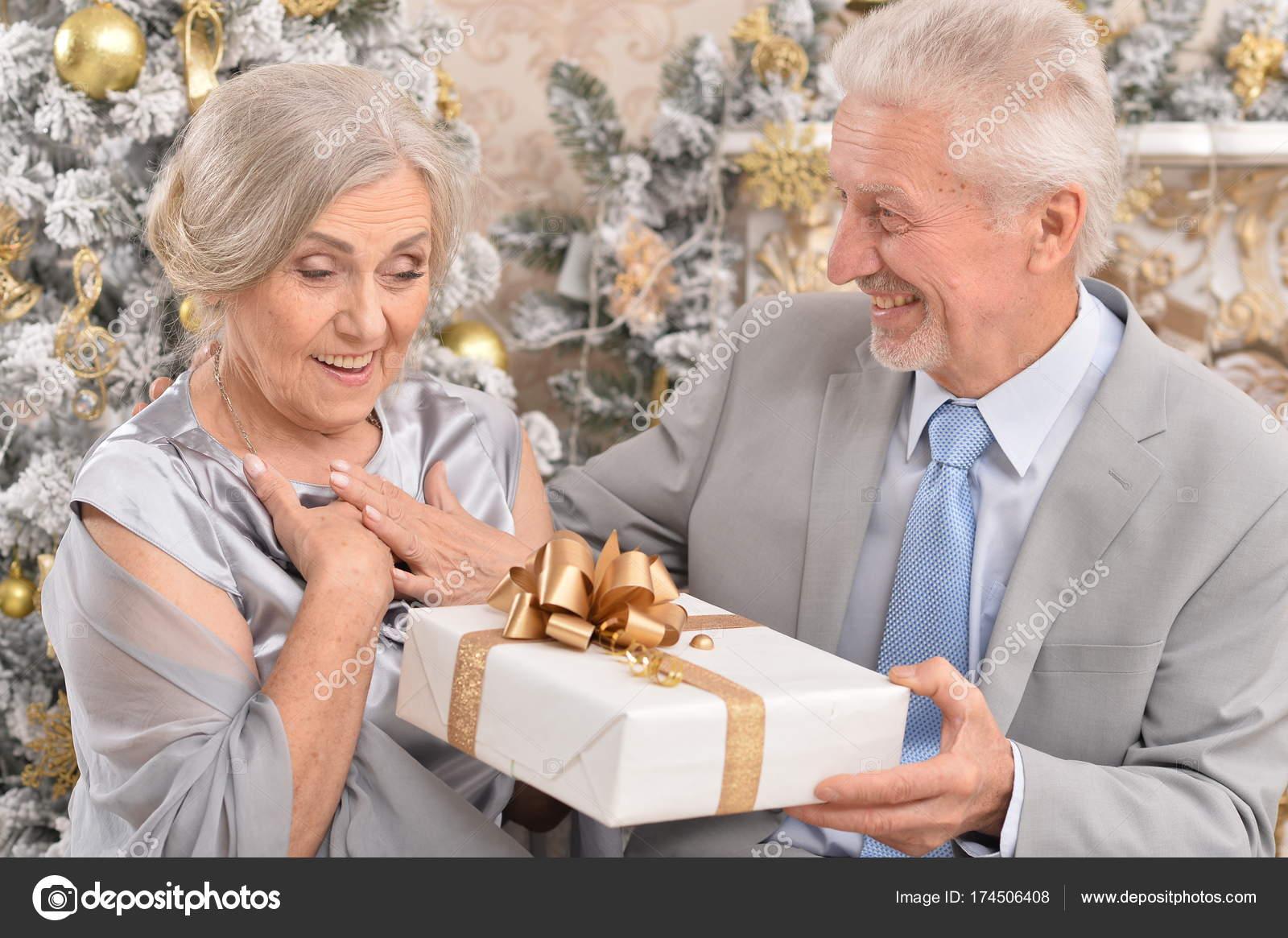 altes Ehepaar mit Weihnachtsgeschenk — Stockfoto © aletia #174506408