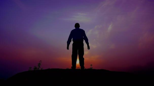 Siluetta di meditazione uomo (preghiera) al top con le mani sollevate al tempo di alba. 4K: 3840 x 2160