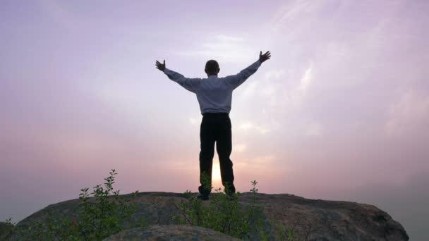 Siluetta delluomo (preghiera) al top con il sole le mani sollevate al tempo di alba