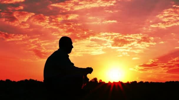regungsloser Mann Tourist sita bei Sonnenaufgang, Sonnenuntergang. 4k 3840x2160