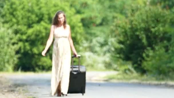 Heißer Sommer und Silhouette einer Frau im Kleid mit Koffer unterwegs.