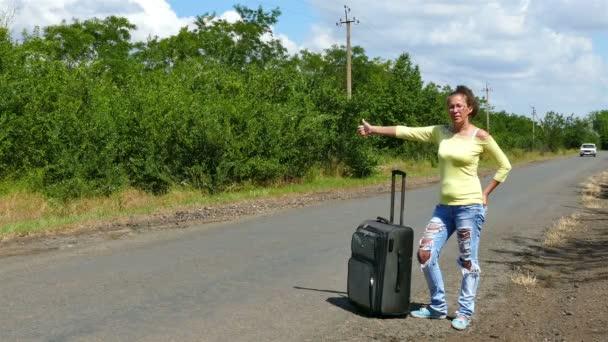 4k. Reife Frau mit Koffer stoppt Auto auf der Straße. Anhalter-Team.