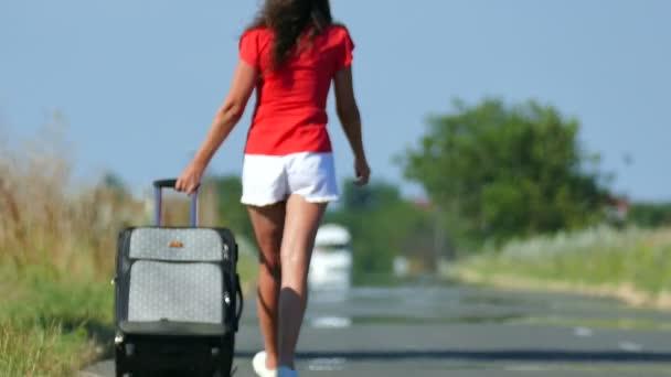 4k. Silhouette einer Frau in roter Bluse mit Koffer unterwegs. Kugelstoßer