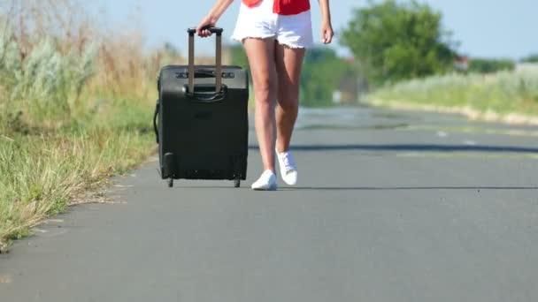 4k. Beine von Frau mit Koffer unterwegs