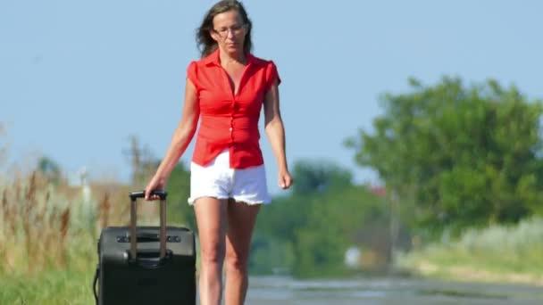 4k. Schlanke Frau mit Koffer im Sommer unterwegs