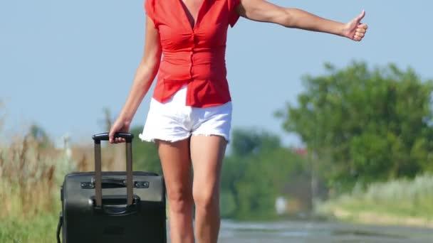 4 k. postava štíhlá žena s kufrem jít na silnici a zastavení auta. Stopování