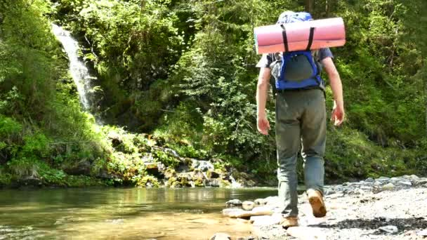 4K .Life in travel . Man  tourist near  river and waterfall . Backpacker team
