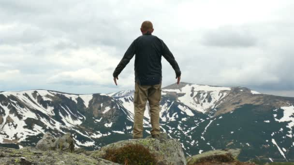 4K. Man  tourist  traveler meditates at mountain top