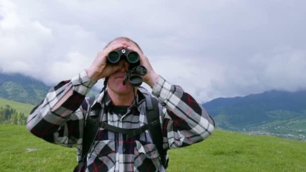 4k. Man-hegység hátizsákos úgy néz ki, a távcső. Fókusz megváltoztatása