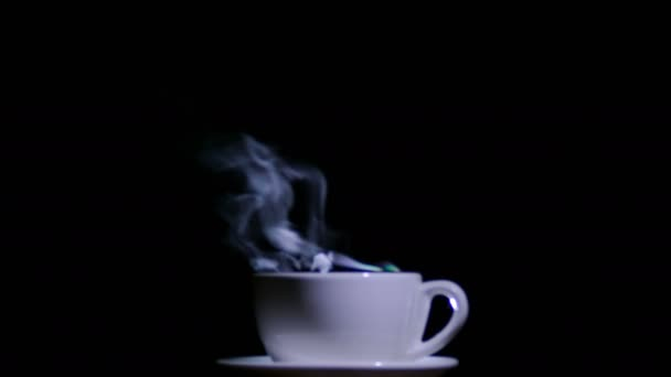 White cup of tea or coffee  with steam on  black background. 4K shot