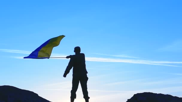 Waves Ukrainian Flag  and Silhouette of Soldier against blue sky .Slow Motion