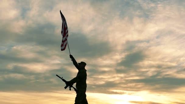 silueta vojáka s vlnou automatická puška americkou vlajku. Zpomalený pohyb.