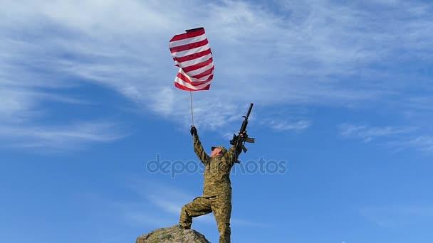 Voják s puškou vlny americkou vlajkou proti modré obloze. Zpomalený pohyb