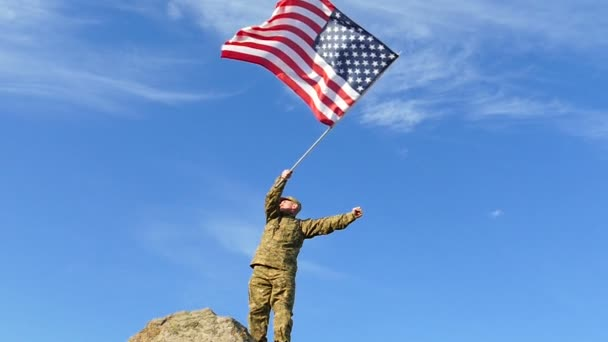 Soldier waves American Flag against blue sky. Slow Motion