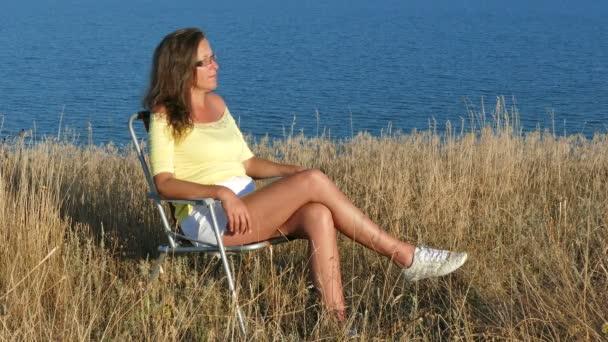 4K. Sexy  harmonious  woman  sits on  chair on  sea coast. Close up