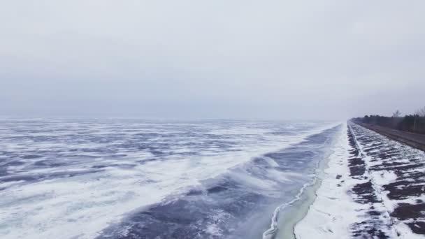 4k letecké. Zimní silnice poblíž zmrzlé moře nebo jezera. Království zimních