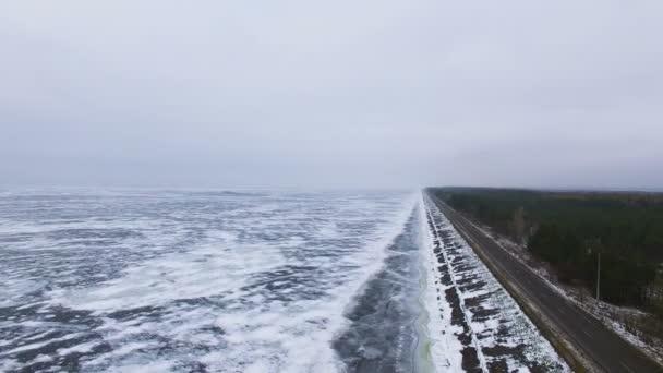 4k letecké. Zimní silnice poblíž zmrzlé moře nebo jezera. Království zimních. Krajina