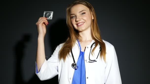 4k. Atraktivní dívka doktor ukazující kondom, úsměv a znamení, že vše je dobré