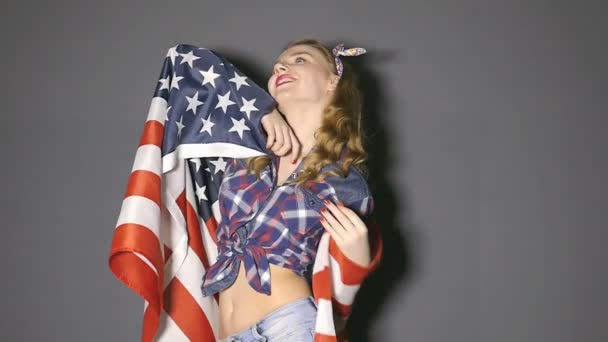 Attractive young girl dances with  American flag and smile. Slow motion