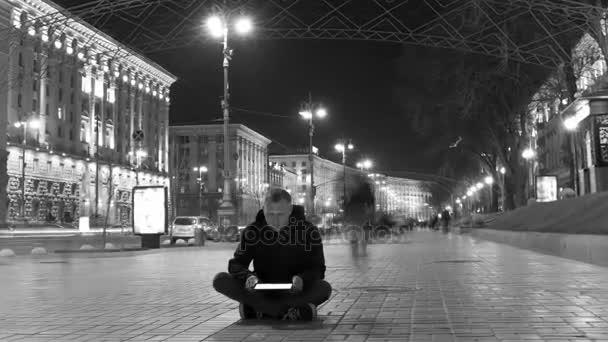 Uomo con la compressa sedersi In fracassato sagoma folla, Time Lapse. Spara cursore bianco e nero