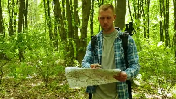 4K.  Man Hiker find way with paper map and compass  in Forest. steady shot