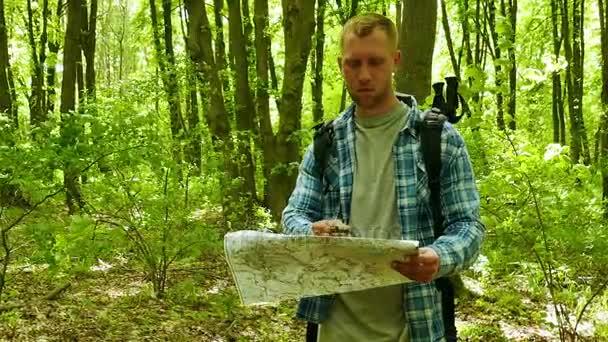 4 k. ember természetjáró keresés módja papír térképpel és tájolóval erdőben. folyamatos lövés