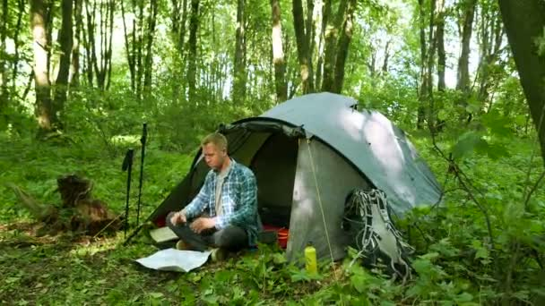 Man tourist with smartphone and paper map near tent in spring forest.u2013 stock footage & 4K. Man tourist with smartphone and paper map near tent in spring ...