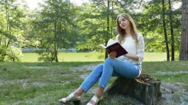 4k.Young modern girl reads  Bible in  summer park. Christian  belief. Slider